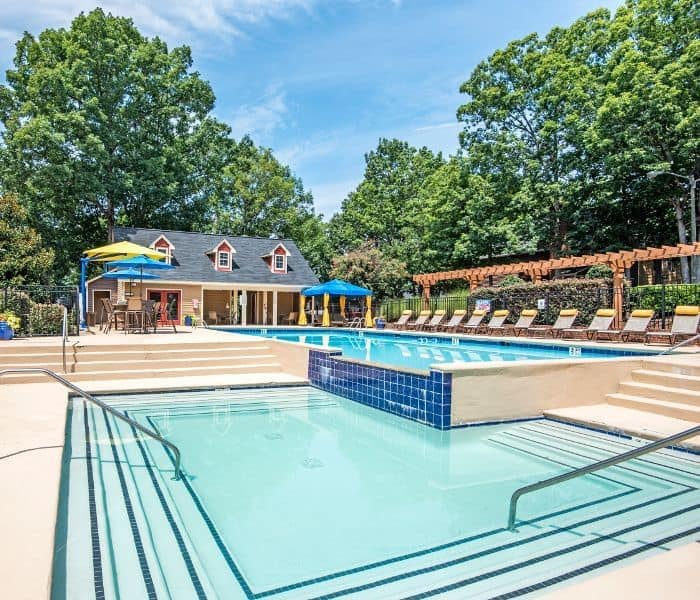 Beautiful, sparkling swimming pool with plenty of chaise lounge chairs at Six Forks Station