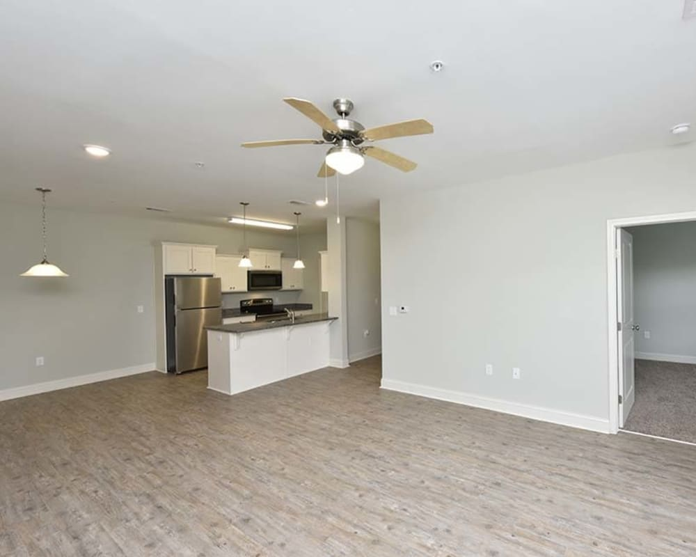 Large open-concept living area with hardwood floors and a ceiling fan in a model home at The Enclave in Brunswick, Georgia