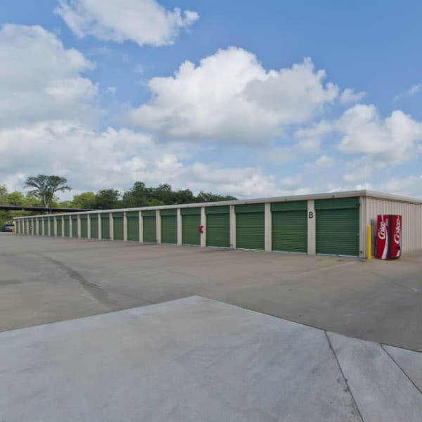 Outdoor storage units with green doors at StorQuest Self Storage in Sugar Land, Texas