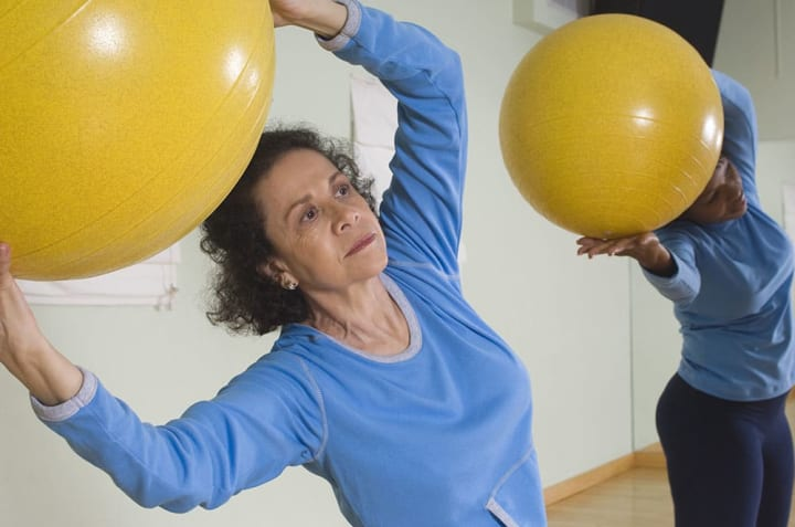 Two female seniors working out with exercise balls.