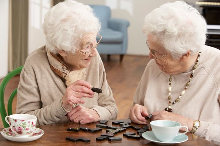 Two residents playing dominoes together at {{location_name}} in {{location_city}}, {{location_state_name}}