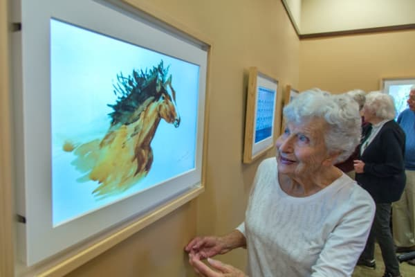 A resident look at a photo at a gallery near Courtyards at Berne Village in New Bern North Carolina