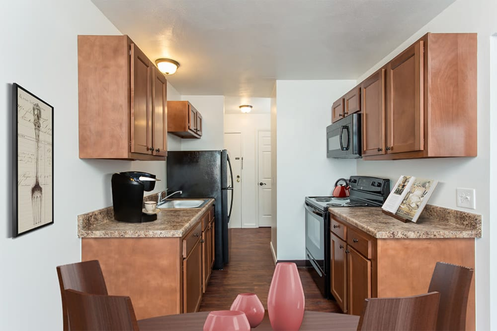 Fully-equipped kitchen with black appliances at Wedgewood West in Rochester, New York