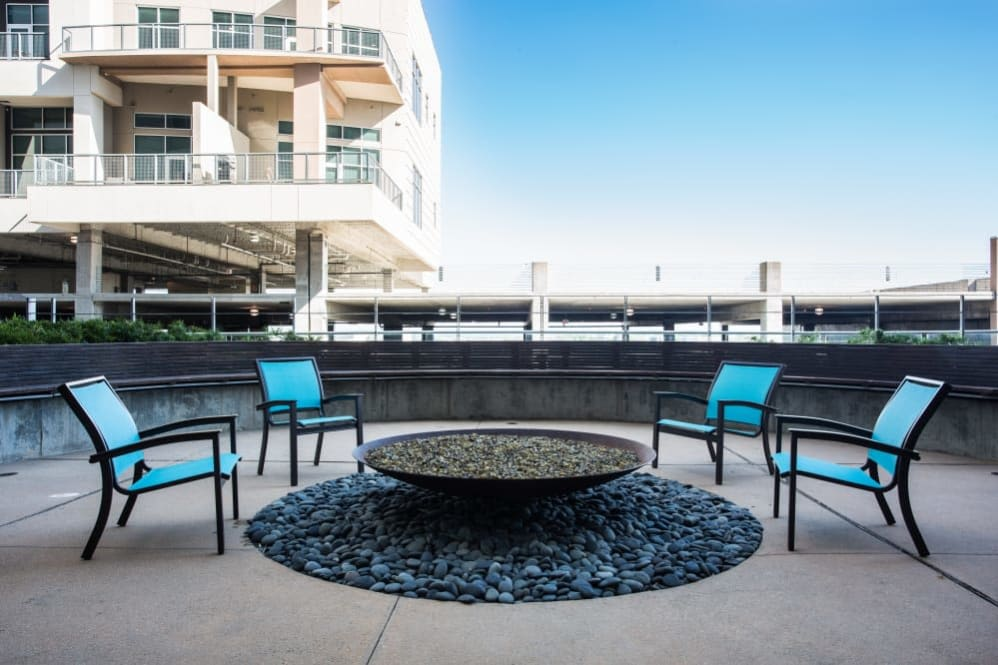 Outdoor fire pit with blue chairs at The Heights at Park Lane in Dallas, Texas