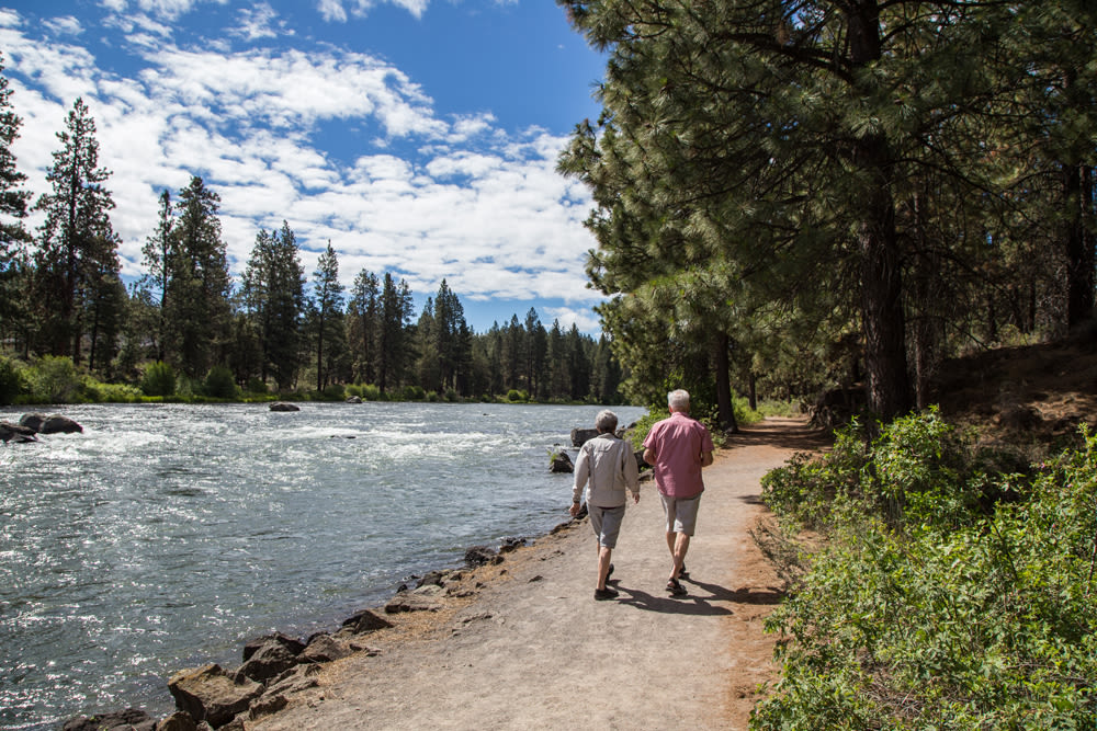 Residents from Touchmark at Mount Bachelor Village in Bend, Oregon walking on a trail along the river