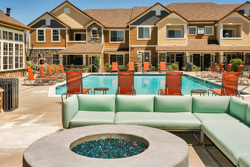 Beautiful fire pit lounge area and resort-style swimming pool with lounge chairs at Crestone Apartments in Aurora, Colorado