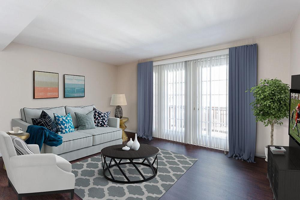Spacious living room with wood-style flooring at Raintree Island Apartments in Tonawanda, New York