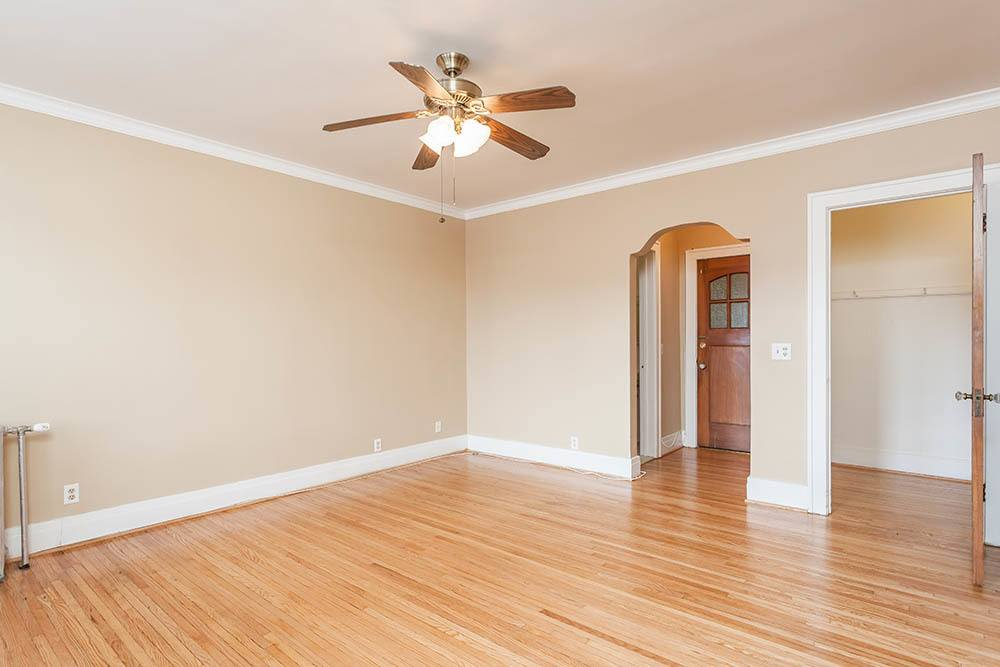 Spacious living room with a ceiling fan at Colby, Carlton, and Colby Park Apartments in Rochester, New York