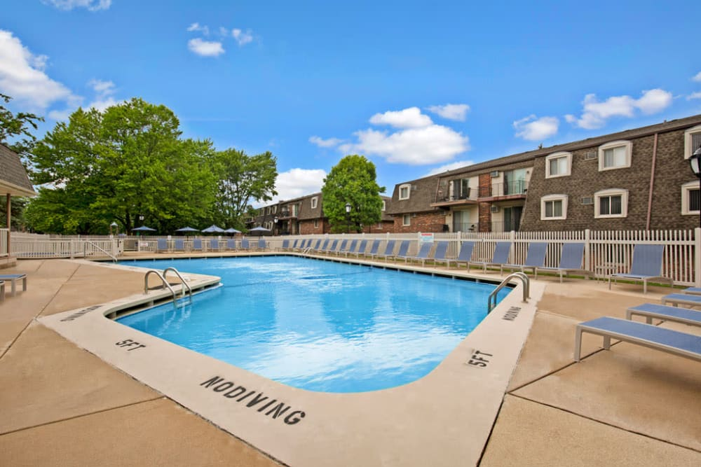 Resident swimming pool with several lounge chairs for sunbathing at Blackhawk Apartments in Elgin, Illinois