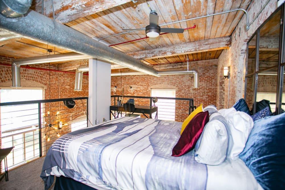 Model loft bedroom at Newnan Lofts Apartment Homes in Newnan, Georgia