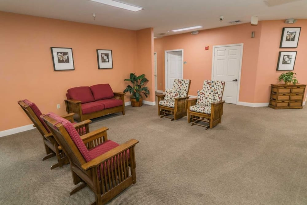 Sitting room with warm peach walls and charming red chairs at RockBrook Memory Care in Lewisville, Texas