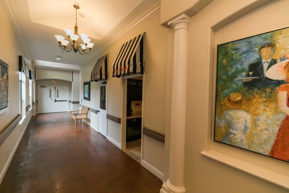 Brightly lit hallway with painting at RockBrook Memory Care in Lewisville, Texas