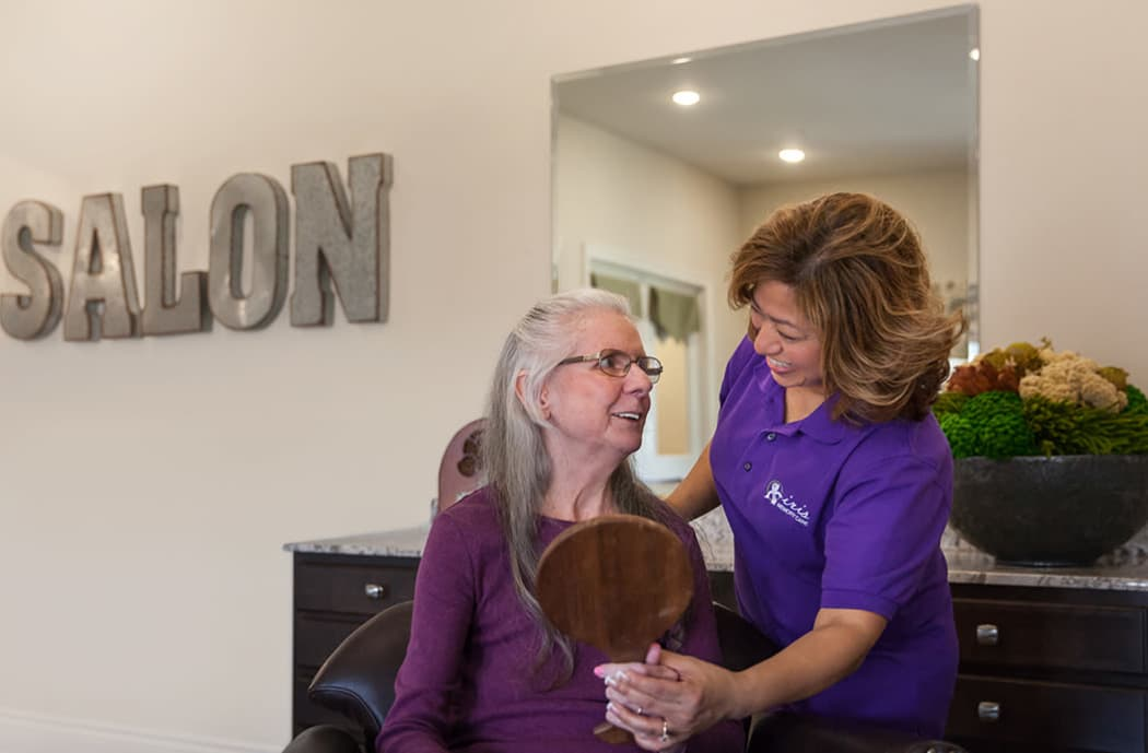 Staff member assisting senior with mirror at Iris Memory Care of Rowlett