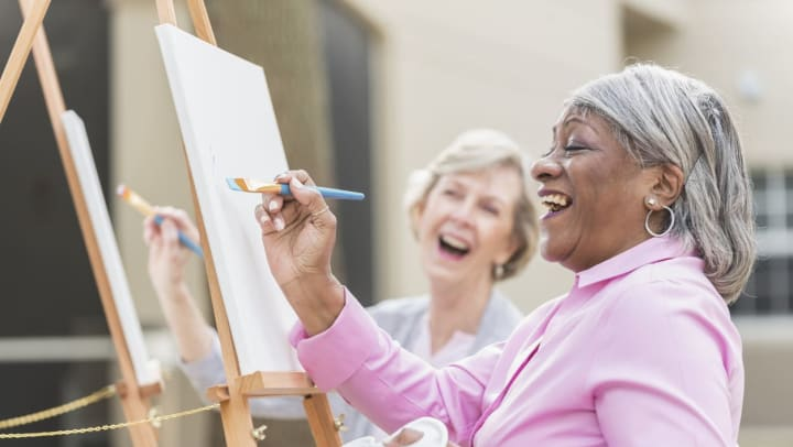 Senior women painting and laughing together