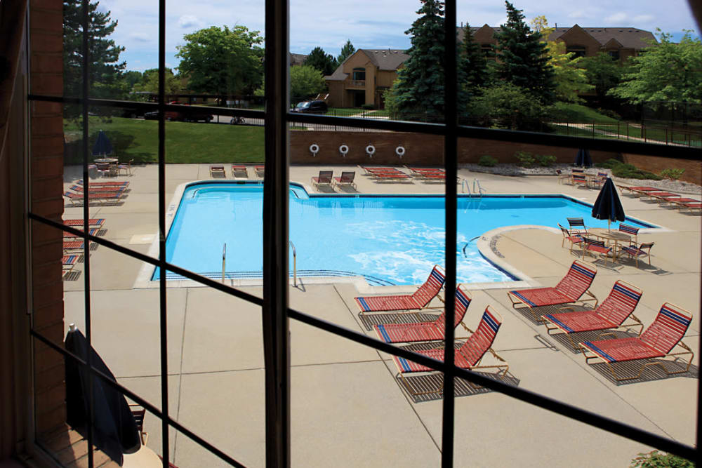 View of the swimming pool area from the clubhouse at Saddle Creek Apartments in Novi, Michigan