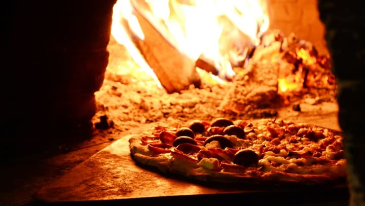A delicious pizza cooking in a wood-fired oven at a restaurant near Olympus Waterford in Keller, Texas.