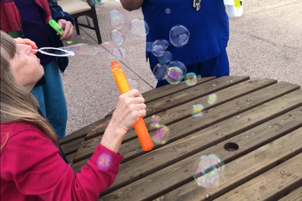 Women blowing bubbles at Woodland Palms Memory Care
