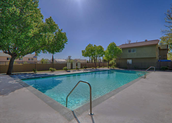 Swimming pool area on a beautiful day at Woodlands West Apartment Homes in Lancaster, CA
