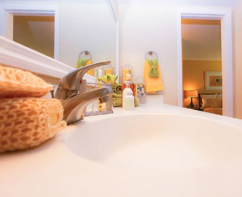 Designer countertop and a large vanity mirror in a model home's bathroom at Signal Pointe Apartment Homes in Winter Park, Florida