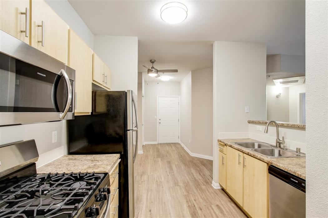Newly remodeled kitchen with granite countertops and stainless-steel appliances in a model home at Sierra Oaks Apartments in Turlock, California