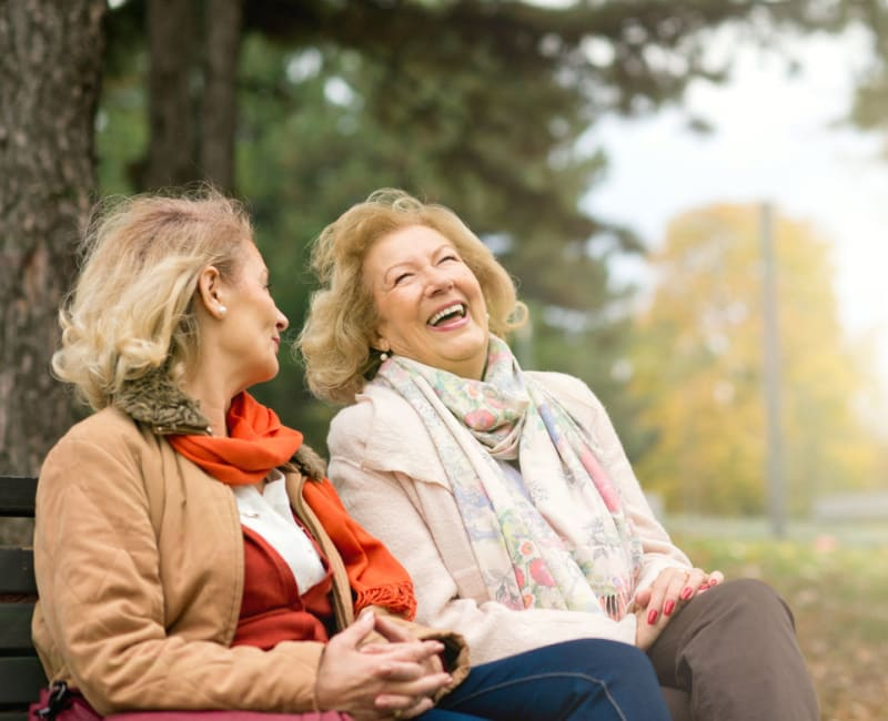 A couple of ladies sitting on a bench outside laughing at York Gardens in Edina, Minnesota