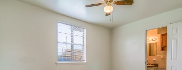 View of empty apartment home bedroom with ceiling fan and ensuite bathroom at Bossier East Apartments