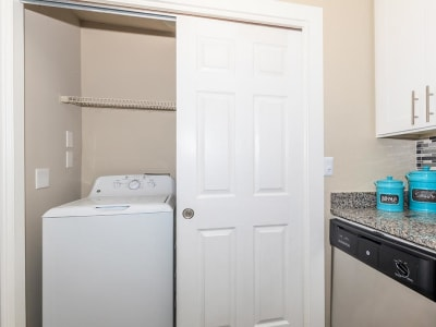 Conveniently located full-size washer and dryer near the kitchen in a model home at The Bentley at Marietta in Marietta, Georgia