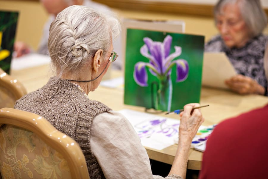 Resident painting some flowers at Palo Alto Commons in Palo Alto, California
