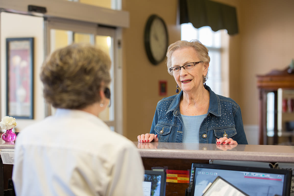 Residents chat with front desk team members at Touchmark on West Century in Bismarck, North Dakota
