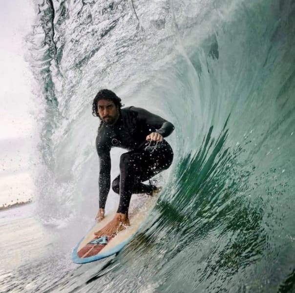 Dr. Cliff Kapono surfing a wave