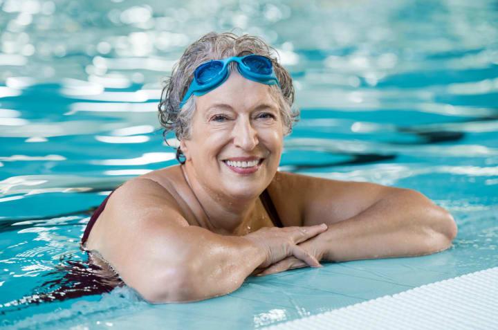 Senior woman in swimming pool smiling