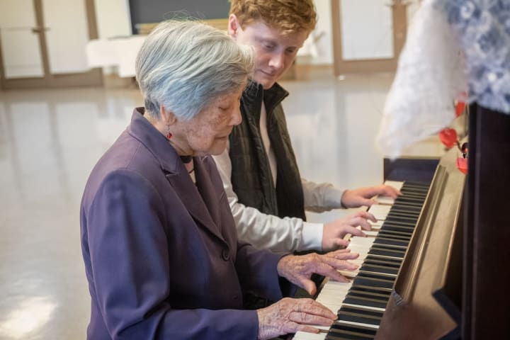 Senior woman playing piano with activities director