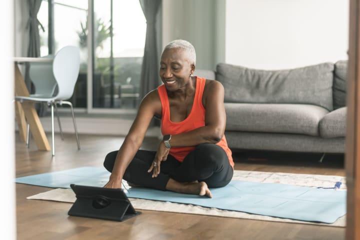 Senior woman taking online yoga class