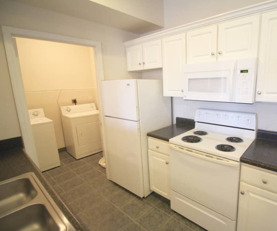 Full-size in-unit washer and dryer next to the kitchen of a model home at Timber Lakes Apartment Homes in Kansas City, Missouri