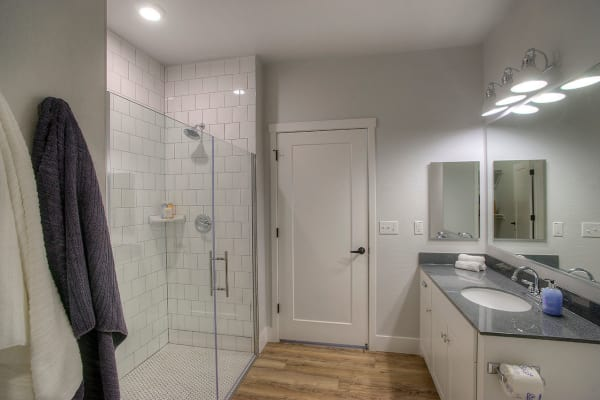 Bathroom with tiled shower and granite countertop in model home at District Lofts in Gilbert, Arizona