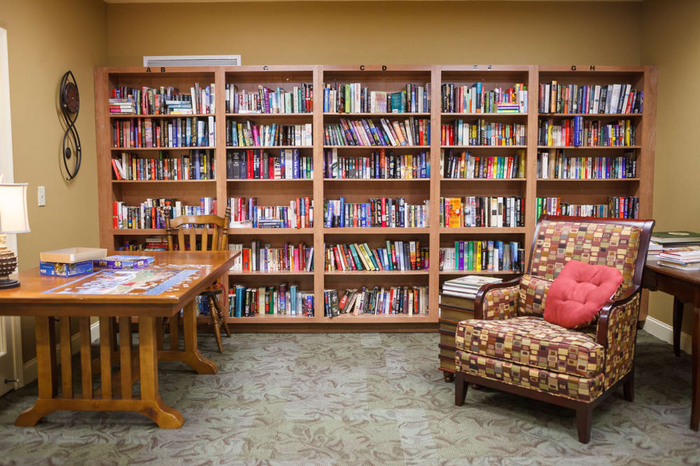 A library with cozy seating at Harmony at Falls Run in Fredericksburg, Virginia