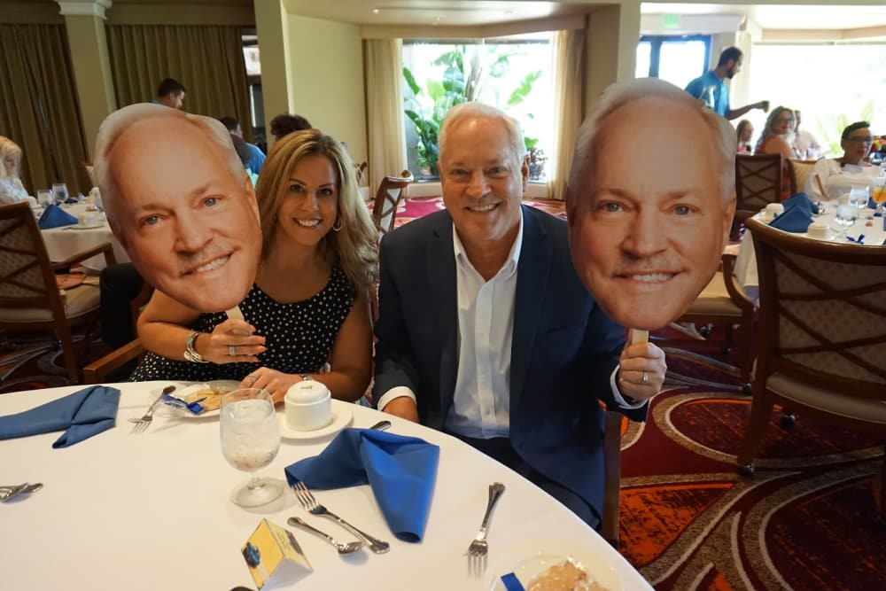 Two people holding giant head cutouts at Discovery Senior Living in Bonita Springs, Florida