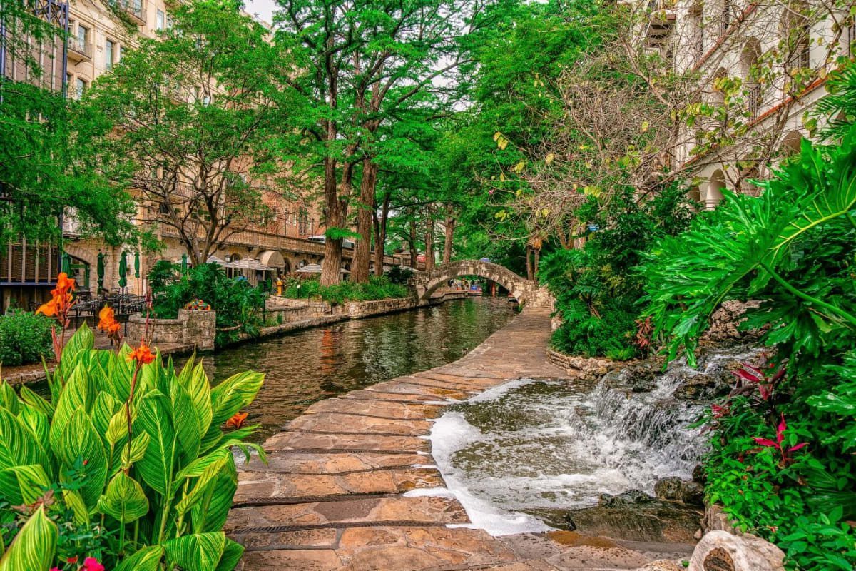 Small stream between two building and surrounded by green trees near Marquis at TPC in San Antonio, Texas