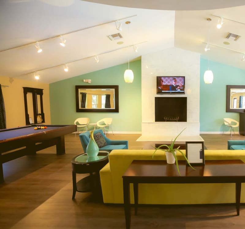Game room with a billiards table and more in the resident clubhouse at Signal Pointe Apartment Homes in Winter Park, Florida