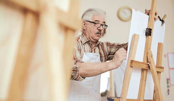 Elderly man working on a painting at Anthology Senior Living in Denver, Colorado