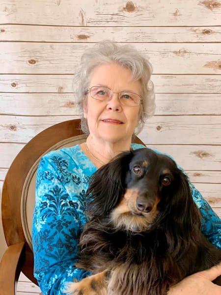 Resident Smiling in blue shirt with dog