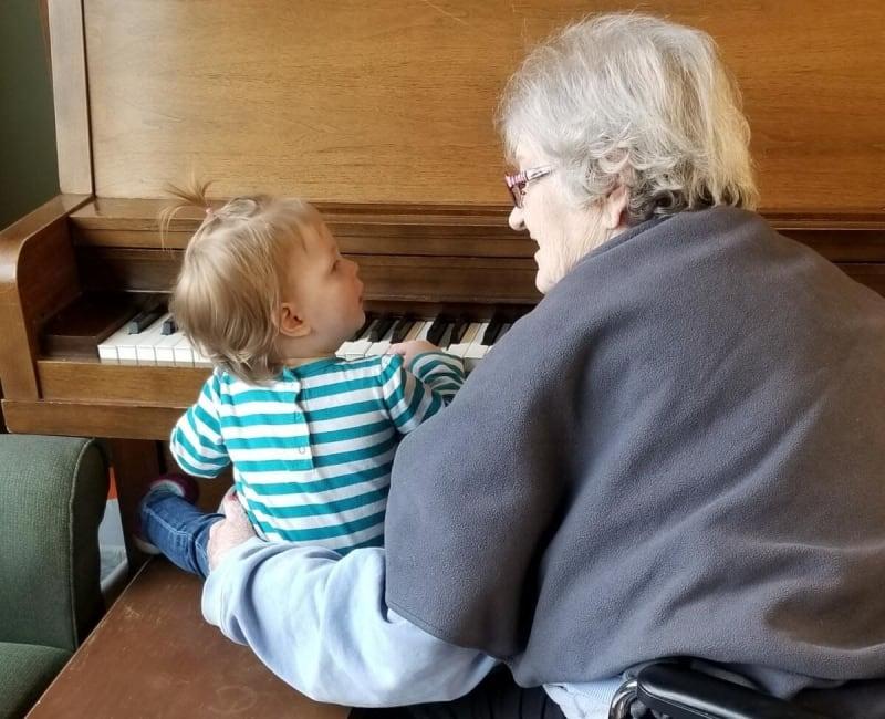 A resident teaching a child the piano at Ebenezer Ridges Campus in Burnsville, Minnesota