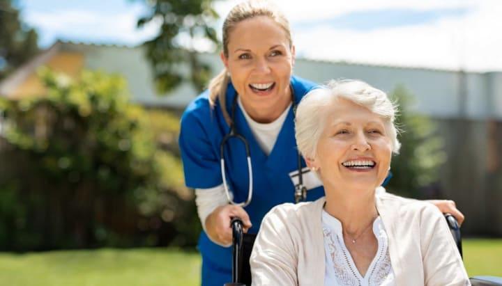 Nurse pushing senior woman in a wheelchair