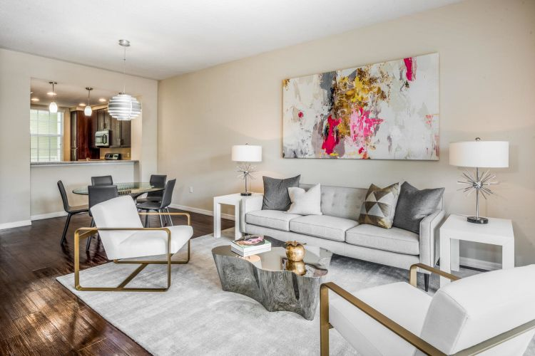Well-decorated living space in an open-concept model senior apartment at Riverwalk Pointe in Jupiter, Florida