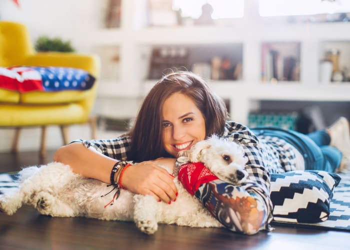 Resident enjoying her new home with her dog at Cypress Townhomes in Marina, California
