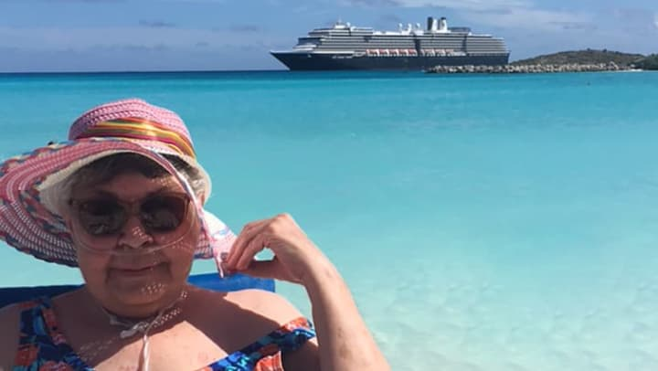 A resident on a beach with the cruise ship behind her