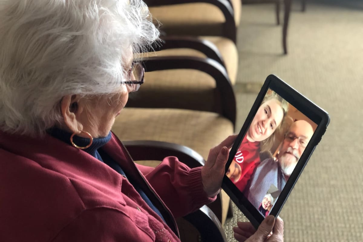 A resident using a tablet to communicate with her family safely at Oxford Glen Memory Care at Grand Prairie in Grand Prairie, Texas