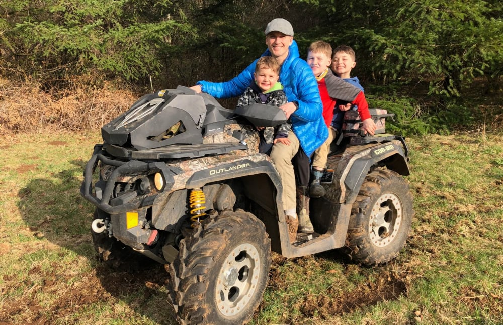 Jim from Touchmark at Meadow Lake Village in Meridian, Idaho and his kids on an ATV