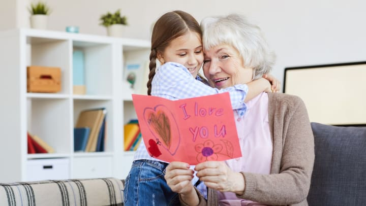 Young girl giving senior woman a Valentine's Day card, hugging and smiling.