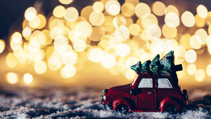 Car-with-Christmas-tree-on-top ornament in snow with blurry twinkling lights in background.